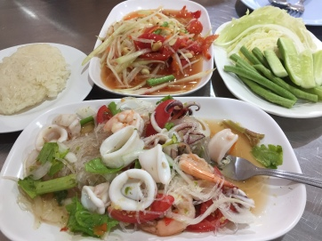 Papaya salad, sticky rice, and seafood with glass noodles.